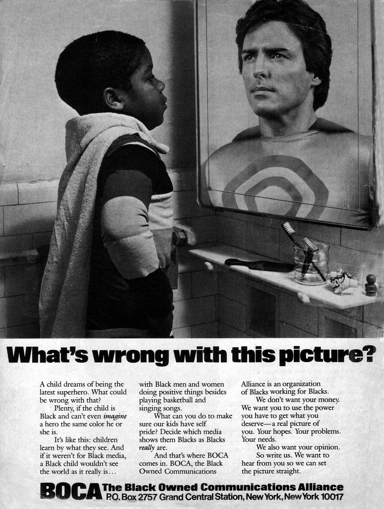 "Newspaper advertisement with an african american boy wearing a towel draped around his neck like a cape. He's standing in a superman pose with his hands at his sides and elbows sticking out. He's looking into a bathroom mirror which is reflecting a white man dressed in a superman type costume. The words written below the picture are ""What's wrong with this picture?"""