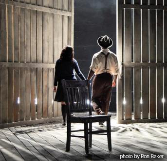 Photo shows an empty wooden chair in the foreground with a boy and a girl holding hands and looking out an open barn door into the darkness.