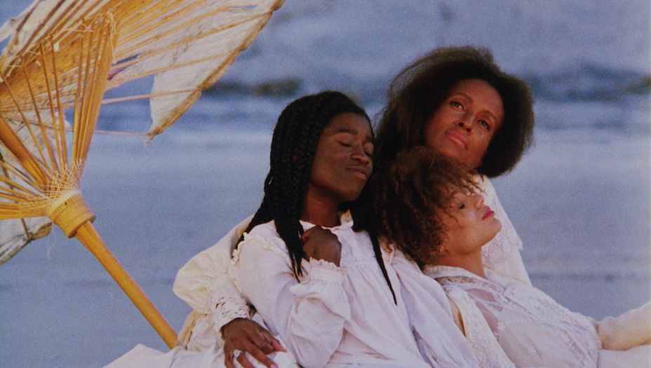 Three black women, all with white clothing, sitting and embracing under a wooden umbrellla at the beach