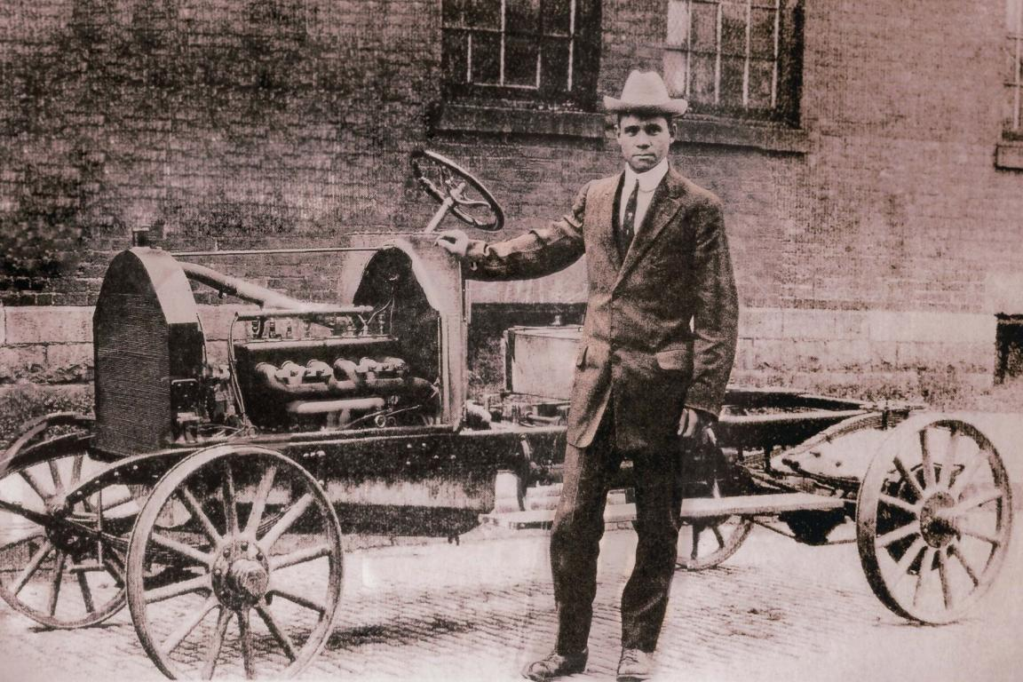 Man standing near early model car
