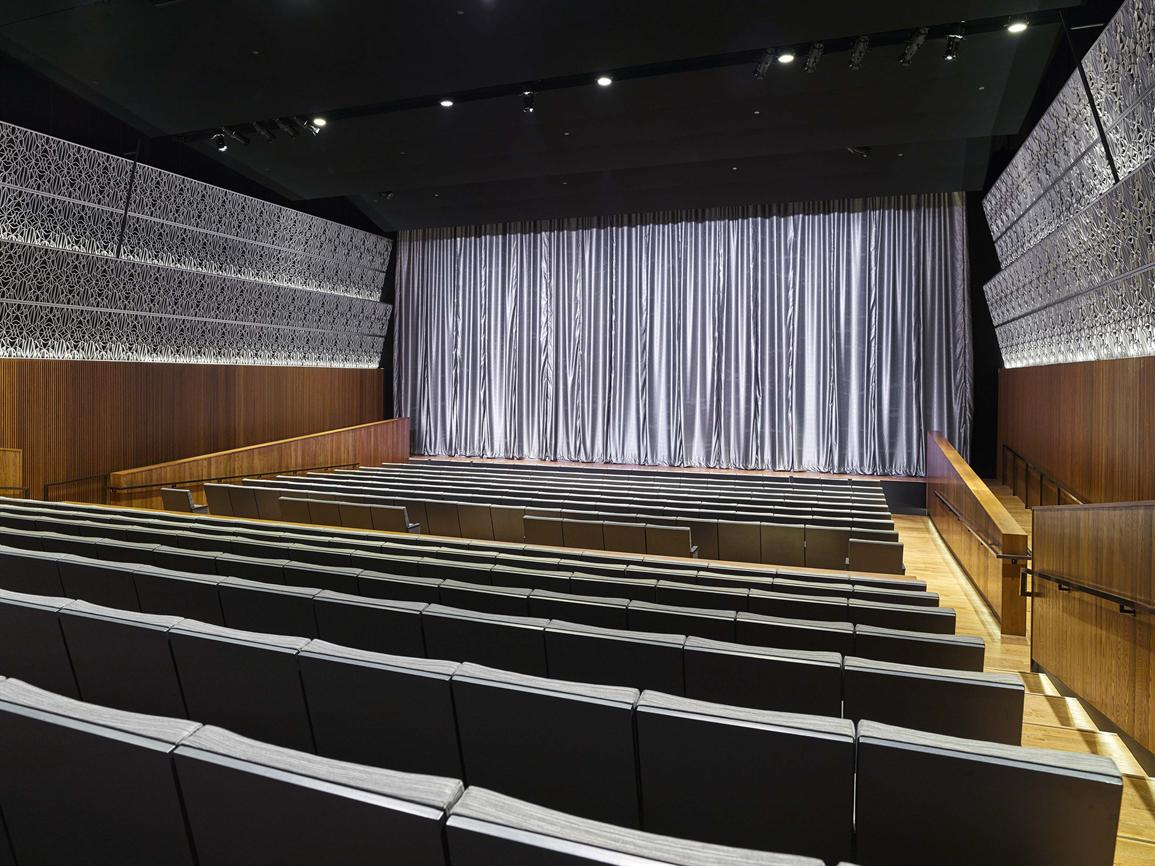 photo of empty Oprah Winfrey Theater at NMAAHC. A silver backdrop curtain is at the back of the stage.