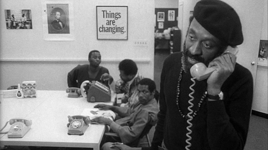 video still from the movie showing a man with a black beret snd long sleeve shirt standing close to the camera talking on a telephone. IN the background are 3 men sitting and working at a table with telephones