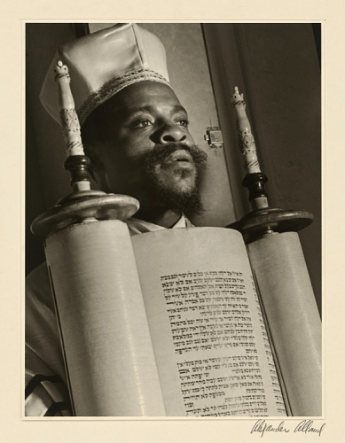 Photo of an African American rabbi in religious dress holding a Torah scroll.