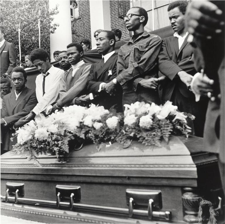 photo showing six black men standing in front of a building and behind a coffin holding hands with crossed arms .