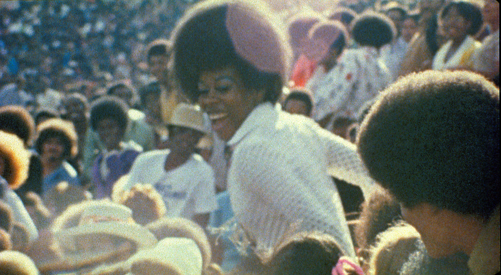 photo of black woman in a large crowd laughing.