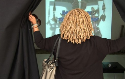 view from behind a woman opening curtains to reveal a motion picture being projected on a wall