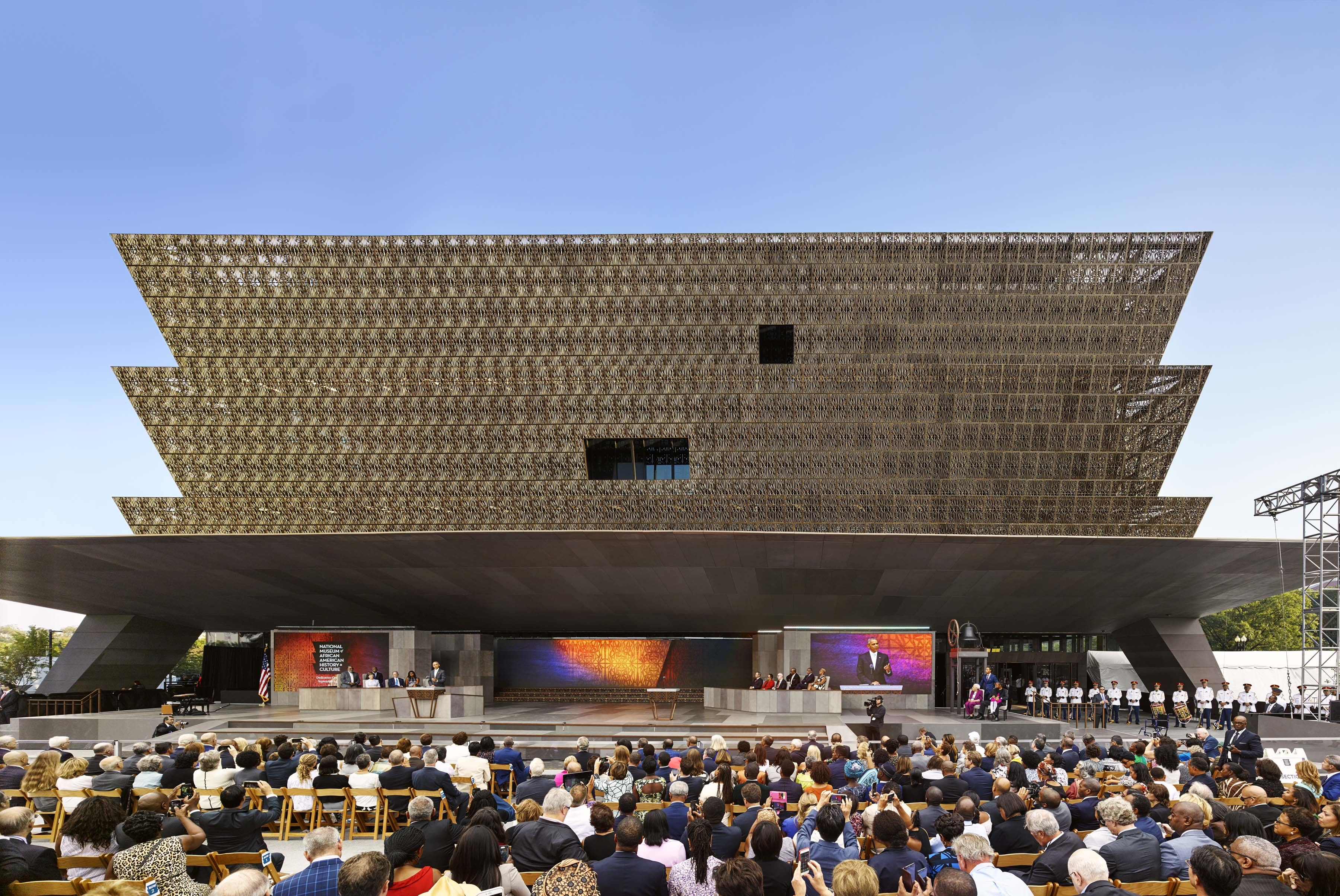 photo of NMAAHC grand opening ceremony with audience in the foreground and the stage and museum building in the background